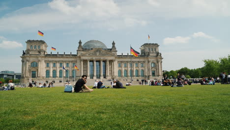 Tourists-And-Locals-Rest-On-A-Green-Lawn-Near-The-Bundestag-Berlin