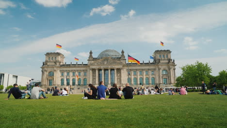 Tourists-And-Locals-Rest-On-The-Lawn-Near-The-Bundestag-In-Berlin-01
