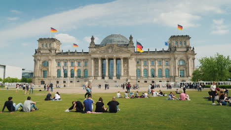 Tourists-And-Locals-Rest-On-The-Lawn-Near-The-Bundestag-In-Berlin-02
