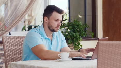 Man-Drinks-Coffee-And-Uses-A-Laptop