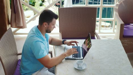 Man-With-Coffee-Cup-Uses-A-Laptop