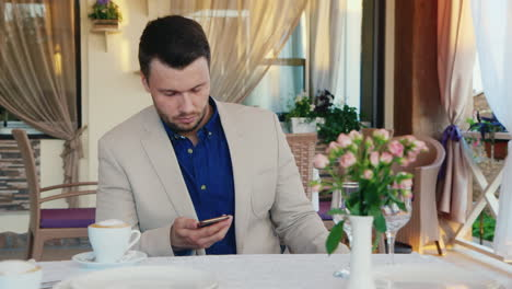 Man-Uses-Smartphone-In-A-Restaurant