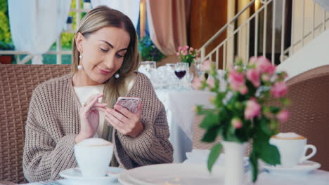 Woman-Uses-Smartphone-In-A-Restaurant