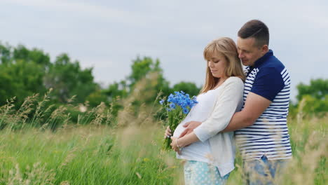 Man-and-Pregnant-Woman-Holding-Flowers