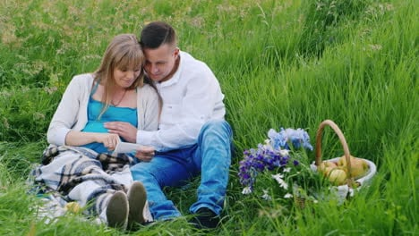 Couple-Look-at-Ultrasound-in-a-Meadow