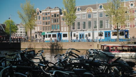 Amsterdam-Canal-With-Bikes-Boat-and-Tram