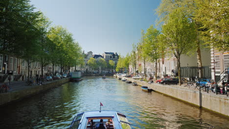 Tour-Boat-Sailing-On-Canal-In-Amsterdam