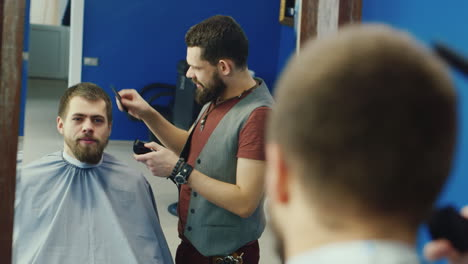 Stylish-Male-Stylist-Cutting-Hair-For-Bearded-Client