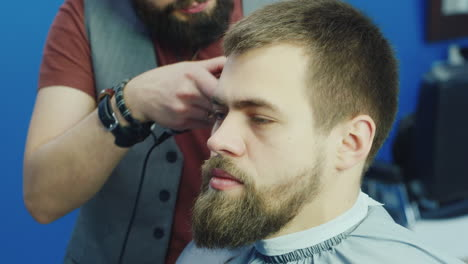 Stylish-Bearded-Hairdresser-Working-In-Salon