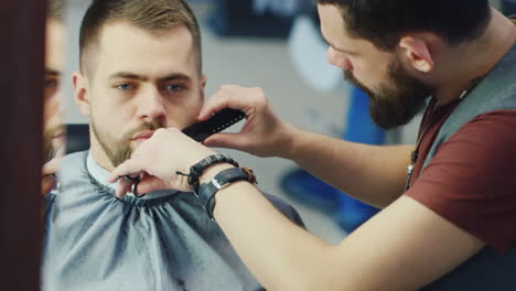 Barber-Cuts-And-Shapes-Client-s-Beard-In-Barbershop