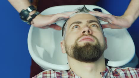 Man-Getting-Hair-Washed-At-Barbershop