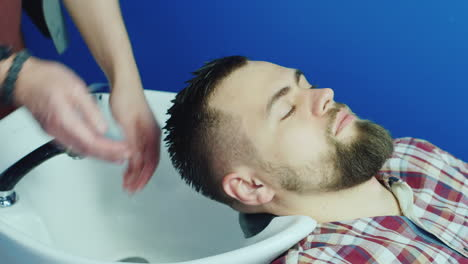 Man-Getting-Hair-Washed-And-Rinsed-In-Barbershop