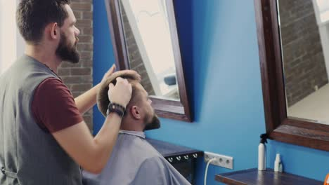 Barber-Applying-Product-To-Client-s-Hair-In-Barbershop