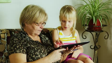 Grandma-And-Granddaughter-Using-Tablet-Together-01