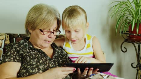 A-Young-Girl-With-A-Grandmother-Using-Tablet