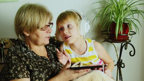 Grandma-And-Granddaughter-Using-Tablet-Together-02
