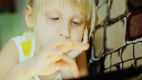 Little-Girl-Using-A-Computer-Tablet-Close-Up-01