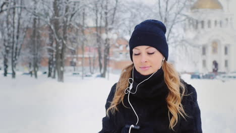 Woman-Walks-And-Listens-To-Music-In-Wintery-Park-01