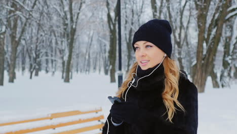 Woman-Walks-And-Listens-To-Music-In-Wintery-Park-02