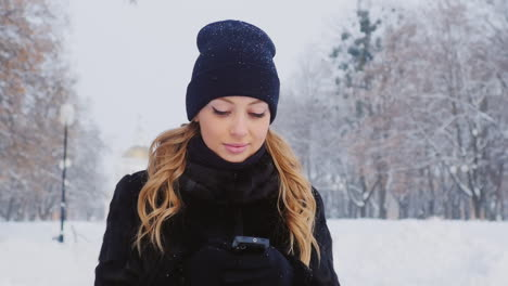 A-Woman-Walks-In-A-Winter-Park-Uses-A-Smartphone