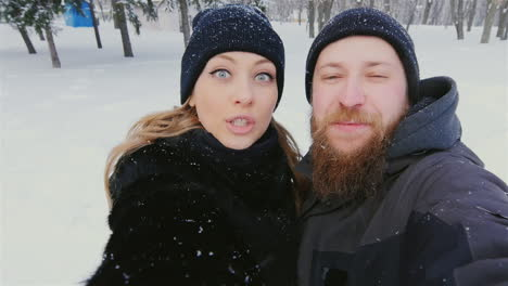 Young-Couple-Have-Fun-In-Winter-Park-Taking-Selfies