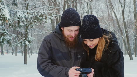 Young-Couple-Viewing-Photos-On-Camera-In-Winter