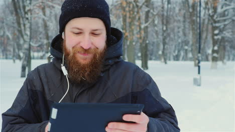 Smiling-Man-Uses-Tablet-In-Winter-Park-01