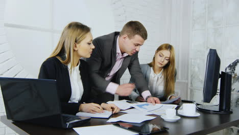 3-business-colleagues-discussing-documents-in-office