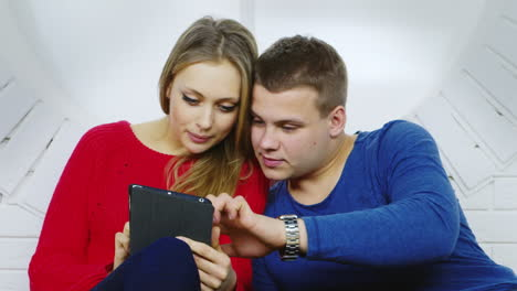 A-Young-Couple-Looking-At-a-Tablet