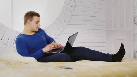 Young-Man-Casually-Using-a-Laptop