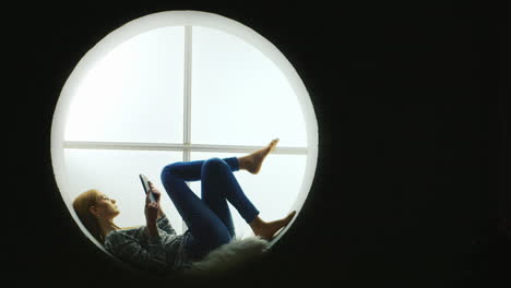 Woman-Sitting-In-a-Round-Window-Uses-Tablet