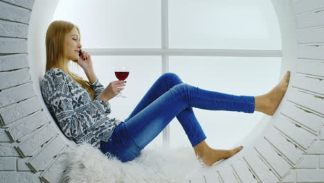 Woman-Sitting-inWindow-on-the-Phone-with-Wine