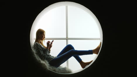 Girl-Sitting-in-Round-Window-Using-Smartphone