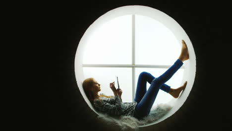 Woman-Relaxing-in-a-Round-Window-Uses-Tablet