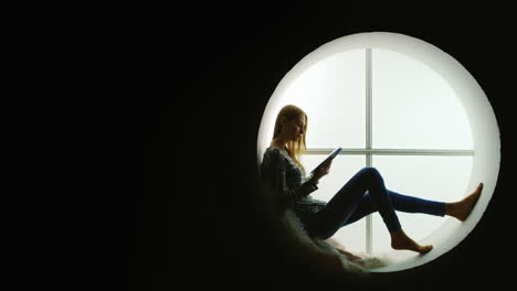 Slender-Woman-Reads-Magazine-In-Round-Window