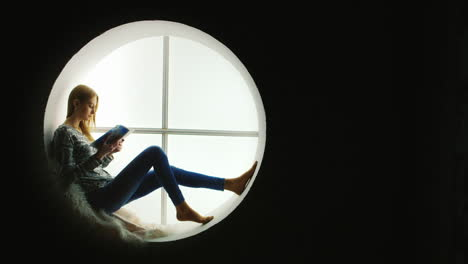 Woman-Reads-Magazine-Sitting-In-Round-Window