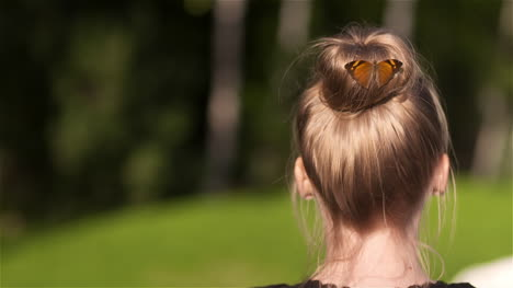 Handheld-Shot-Of-Butterfly-On-Bun-Of-Woman-At-Park