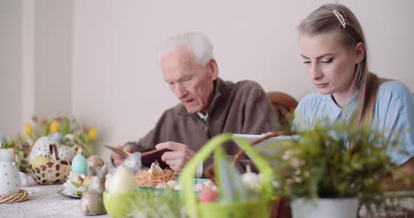 Panning-Shot-Of-Father-Praying-While-Daughter-Using-Digital-Tablet-At-Table-During-Easter