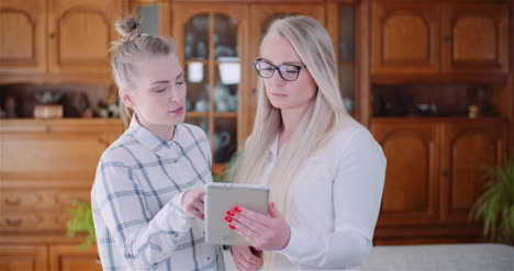 Female-Coworkers-Discussing-Over-Digital-Tablet-In-Office