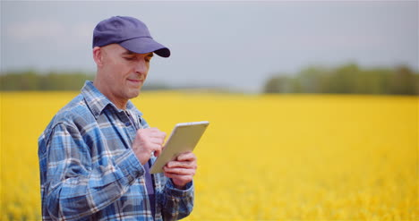 Farmer-Examining-Agricultural-Field-While-Working-On-Digital-Tablet-Computer-At-Farm-3