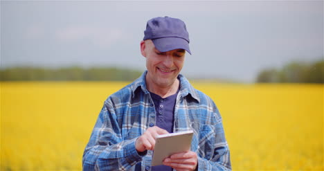Farmer-Examining-Agricultural-Field-While-Working-On-Digital-Tablet-Computer-At-Farm-4