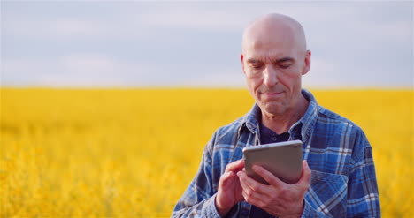 Agriulture-Farmer-Using-Digital-Tablet-Computer-Against-Yellow-Rapeseed-Field-At-Farm-1