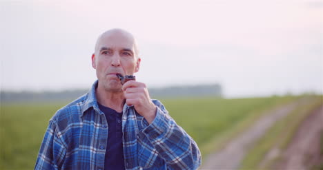 Contented-Bald-Farmer-Smoking-His-Pipe-On-Field