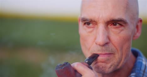 Contented-Bald-Farmer-Smoking-His-Pipe-On-Field-1