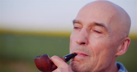 Contented-Bald-Farmer-Smoking-His-Pipe-On-Field-2