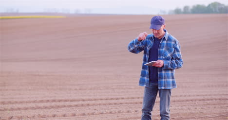Farmer-Examining-Young-Plants-At-Agricultural-Field-1