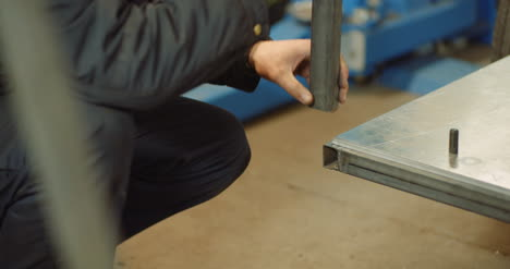 Man-Working-At-Metal-Industry-Cutting-And-Measuring-Metal-Parts-At-Workshop-1