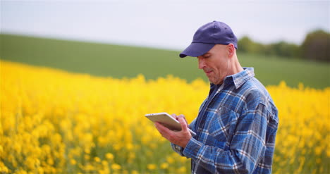 Agriculture-Technology-Concept-Farmer-Examining-Agriculture-Field-Working-On-Digital-Tablet-