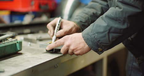 Man-Working-At-Metal-Industry-Cutting-And-Measuring-Metal-Parts-At-Workshop-4