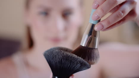 Young-Woman-Using-Brush-And-Powder-While-Doing-Make-Up-